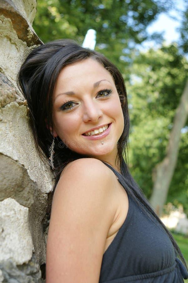 Jeune femme de sourire de brune posant dehors photo stock
