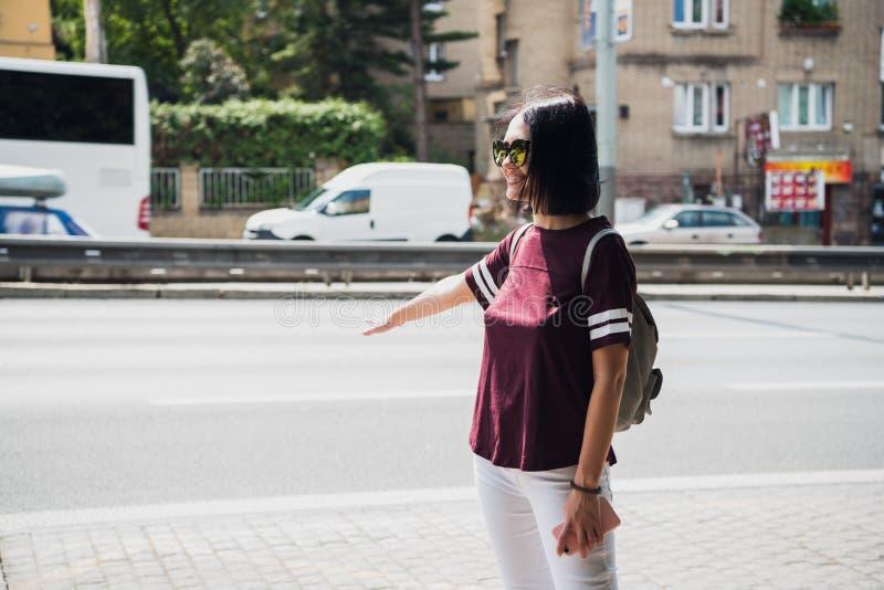Jeune femme de sourire de charme dans des lunettes de soleil faisant des gestes tout en presque se tenant à la route pour arrêter photos stock