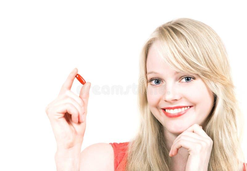 Jeune femme de sourire convenable avec la pilule ou le comprimé de médecine image stock