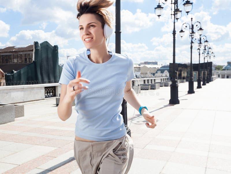 Jeune femme de sourire courant sur le pont au-dessus du paysage urbain photographie stock