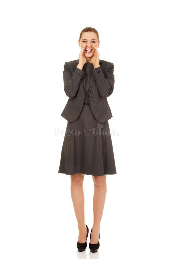 Jeune femme de sourire d'affaires criant fort ou appelle quelqu'un photographie stock libre de droits