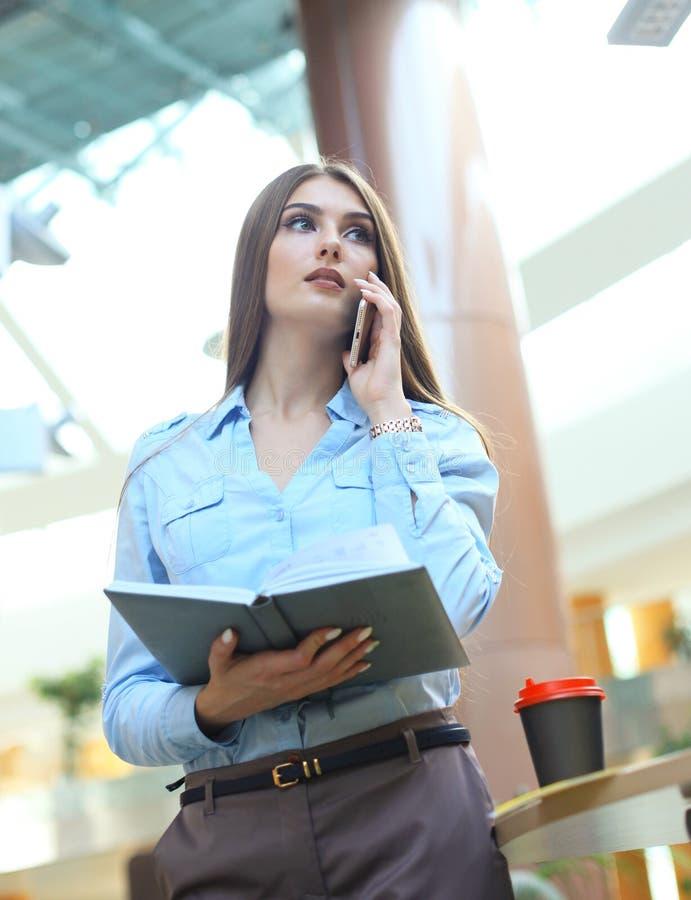 Jeune femme de sourire d'affaires parlant par le téléphone, tenant le journal intime dans le bureau photos stock