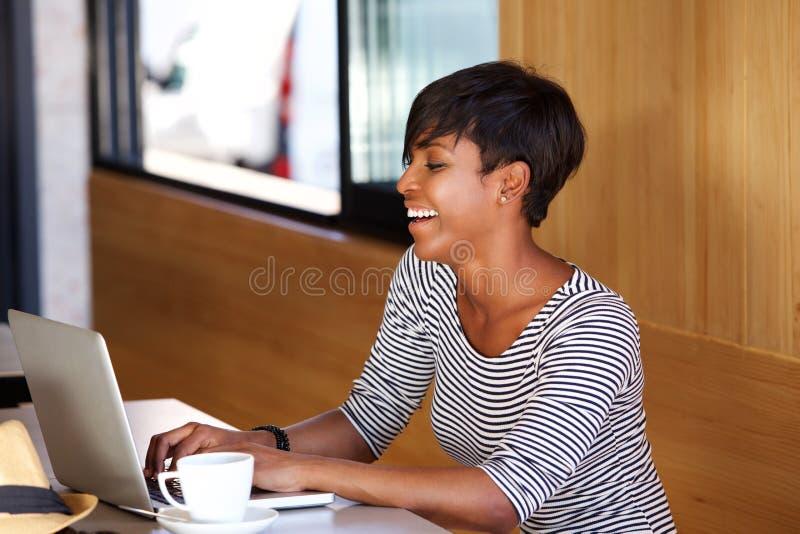 Jeune femme de sourire d'afro-américain à l'aide de l'ordinateur portable photographie stock libre de droits