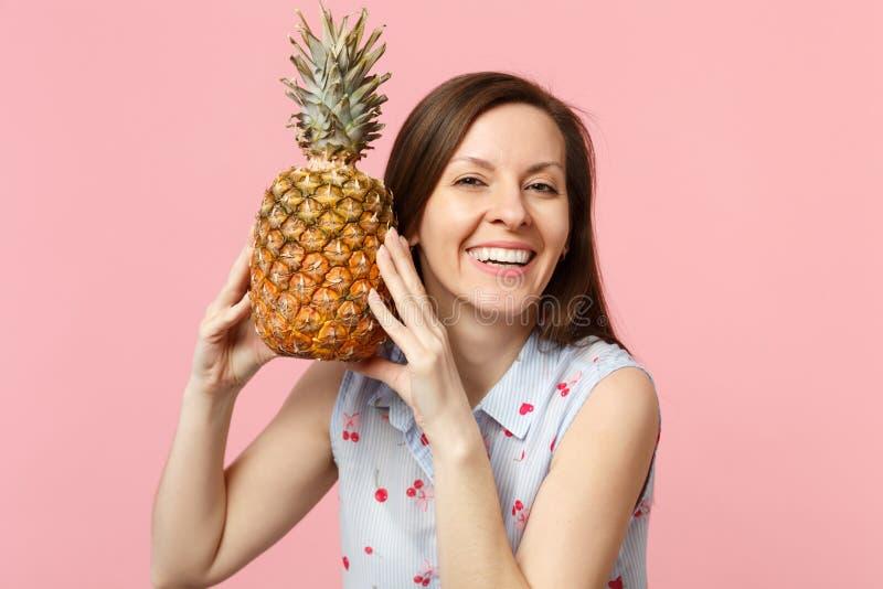 Jeune femme de sourire dans des vêtements d'été se tenant en fruit mûr frais d'ananas de mains d'isolement sur le mur en pastel r image stock