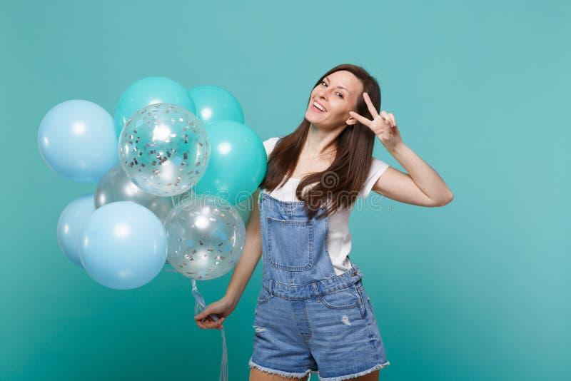 Jeune femme de sourire dans des vêtements de denim montrant le signe de victoire, célébrant et jugeant les ballons à air colorés  images stock