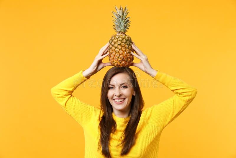 Jeune femme de sourire dans des vêtements sport tenant le fruit mûr frais d'ananas sur la tête d'isolement sur le mur jaune-orang photos libres de droits