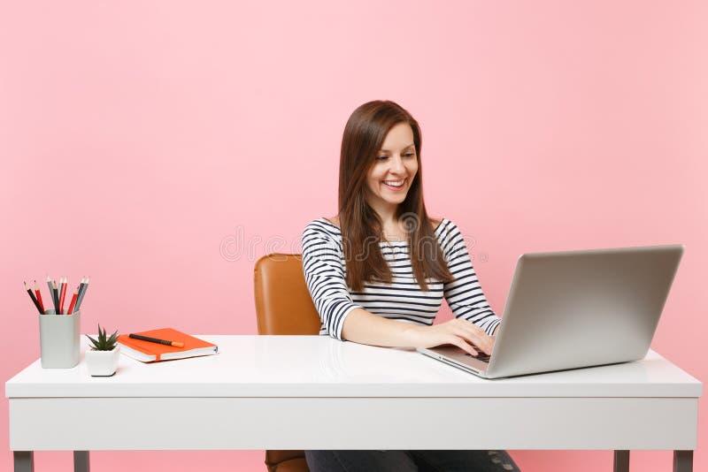 Jeune femme de sourire dans des vêtements sport travaillant sur le projet tout en se reposant au bureau avec l'ordinateur portabl image stock