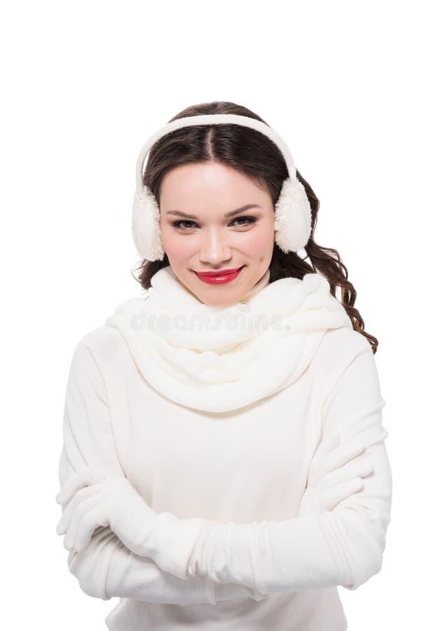 jeune femme de sourire dans l'écharpe, les gants et les bouche-oreilles posant avec des bras croisés et regardant l'appareil-phot image libre de droits