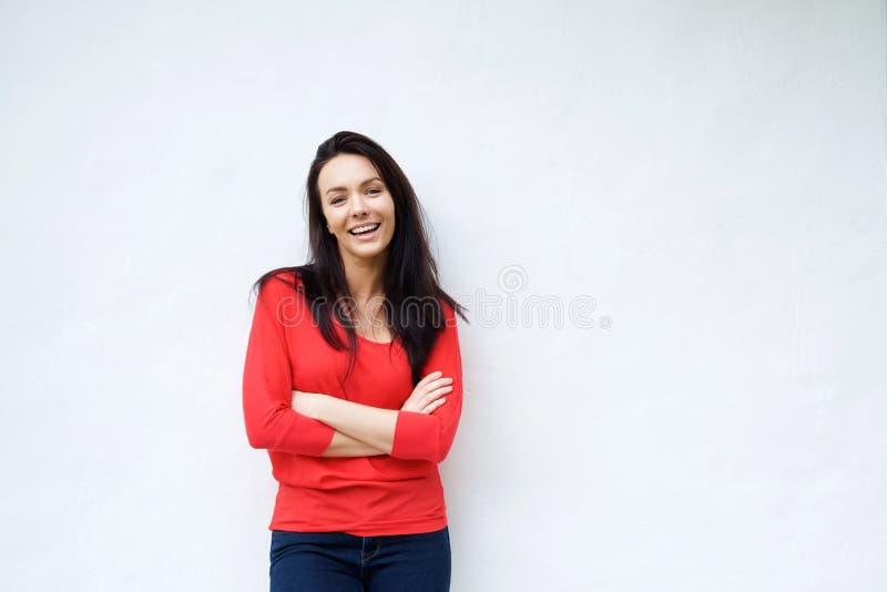 Jeune femme de sourire dans la chemise rouge souriant sur le fond blanc image stock