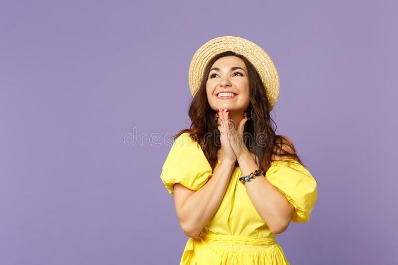 Jeune femme de sourire dans la robe jaune, chapeau d'été recherchant, mains pliées faisant le souhait, priant sur la violette en  image libre de droits