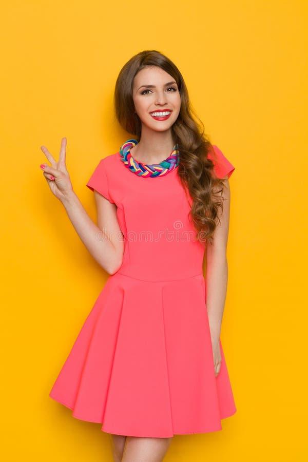 Jeune femme de sourire dans la robe rose montrant le signe de paix photo libre de droits
