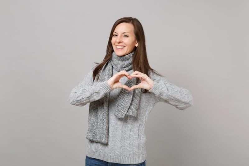 Jeune femme de sourire dans le chandail gris, écharpe montrant le coeur de forme avec des mains sur le fond gris de mur Sain photo stock