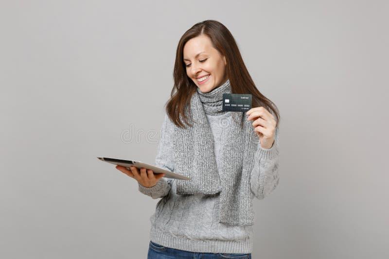 Jeune femme de sourire dans le chandail gris, écharpe utilisant l'ordinateur et juger de PC de comprimé la carte de banque de cré photos stock