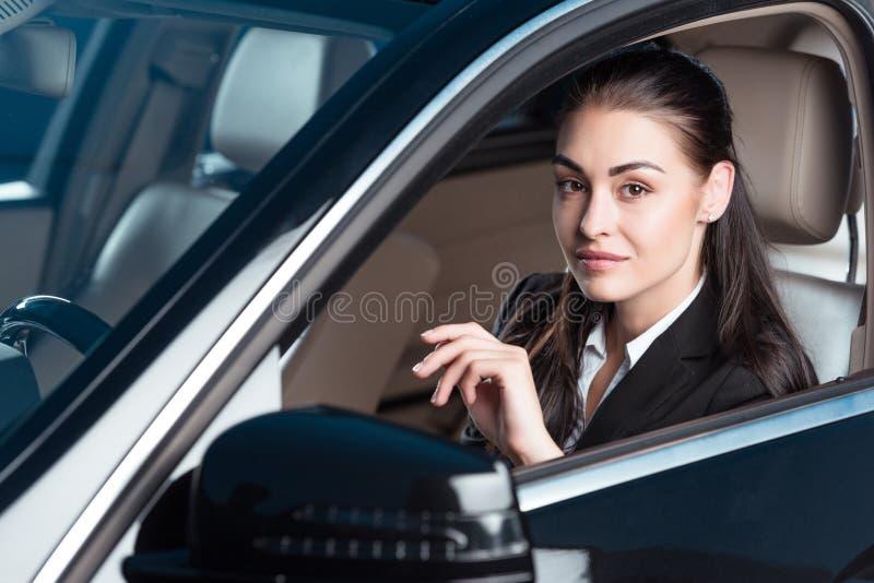 Jeune femme de sourire dans le costume se reposant dans le siège de conducteurs d'une voiture et d'un regard de tourisme photos stock