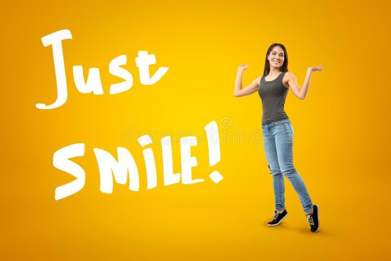 Jeune femme de sourire dans le dessus gris et blues-jean se tenant sur la pointe des pieds avec des bras pli?s et augment?s aux c illustration stock