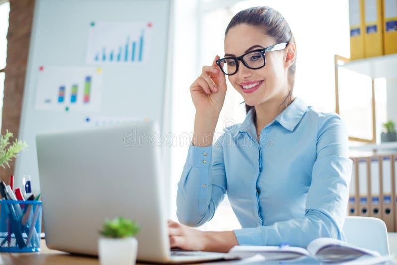 Jeune femme de sourire dans le formalwear au travail se reposant à la table a photographie stock