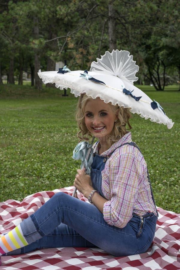Jeune femme de sourire dans le pique-nique avec le parapluie image libre de droits