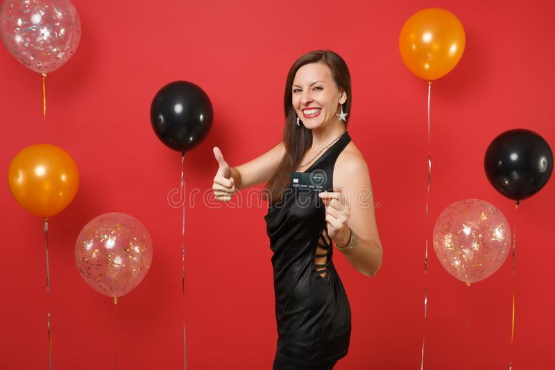 Jeune femme de sourire dans peu de robe noire célébrant, tenant la carte de crédit, montrant le pouce sur le fond rouge lumineux images libres de droits