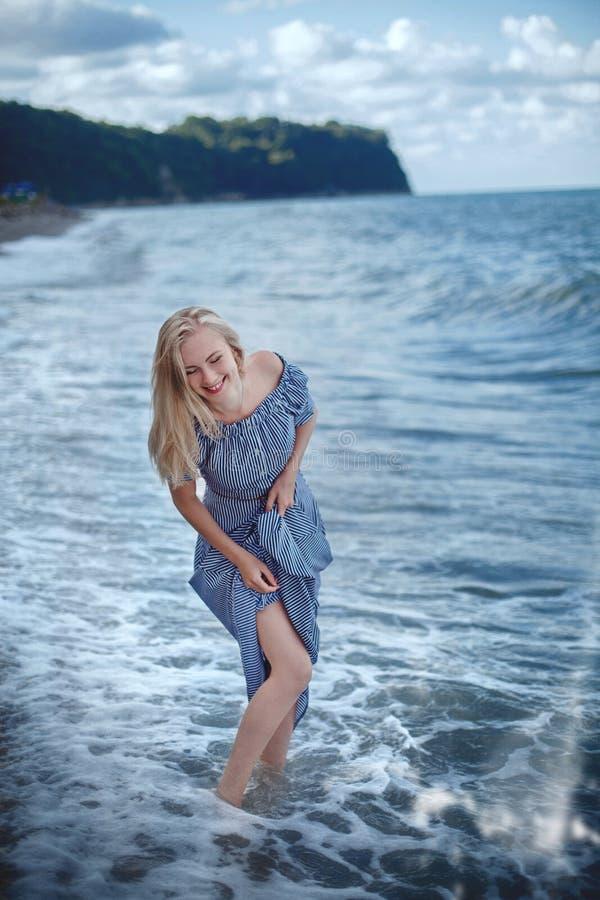 Jeune femme de sourire dans une longue robe image libre de droits