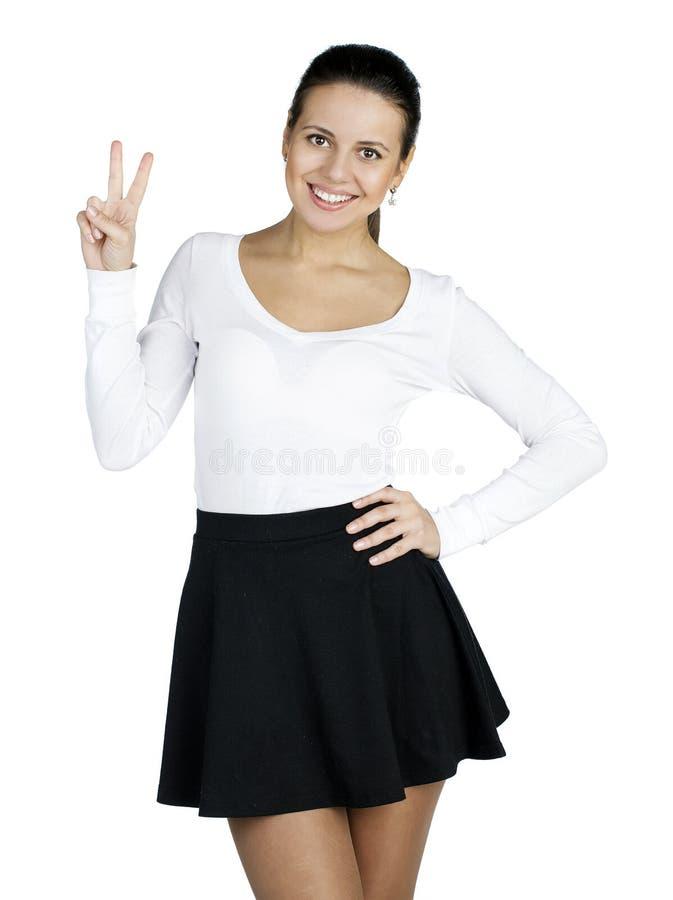 Jeune femme de sourire de brune montrant le signe de victoire ou de paix photographie stock libre de droits