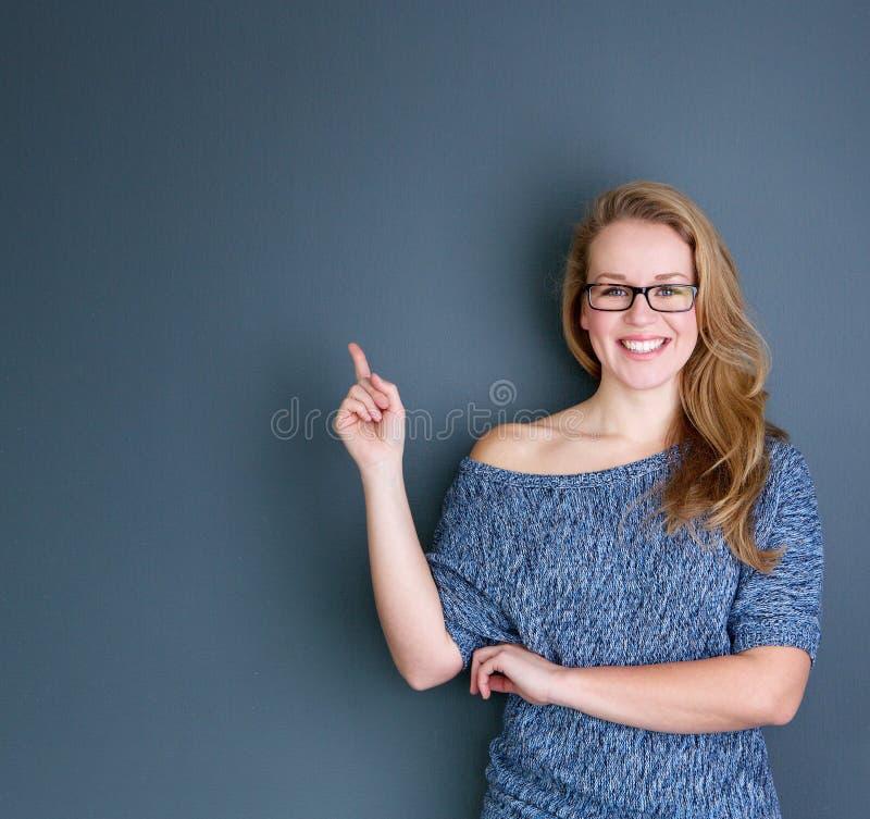 Jeune femme de sourire dirigeant le doigt images libres de droits