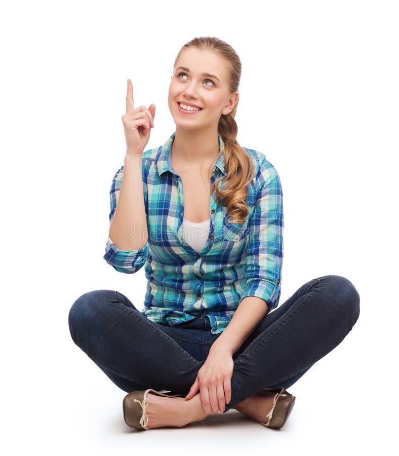 Jeune femme de sourire dirigeant le doigt  image libre de droits