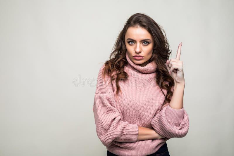 Jeune femme de sourire dirigeant le doigt au-dessus du fond gris photo libre de droits