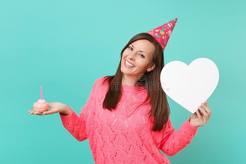 Jeune femme de sourire en gâteau rose tricoté de prise de chapeau d'anniversaire de chandail à disposition avec la bougie, coeur  images stock
