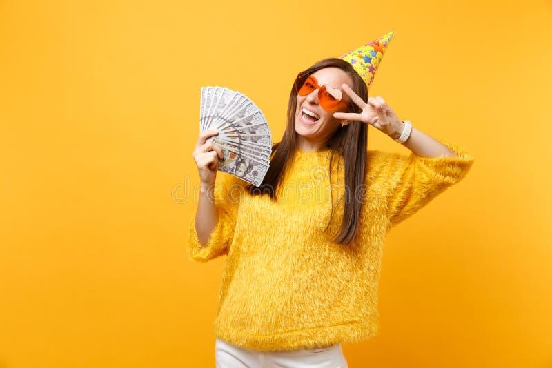 Jeune femme de sourire en verres oranges de coeur, signe de victoire d'apparence de chapeau d'anniversaire, célébrant tenant beau image libre de droits