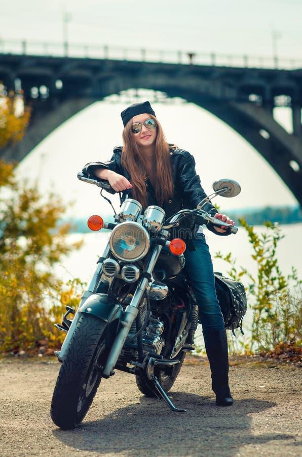 Jeune femme de sourire en veste en cuir et verres sur un motorcy photos stock