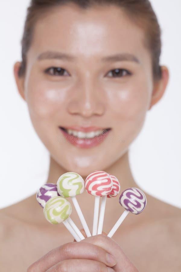Jeune femme de sourire examinant l'appareil-photo et supporter les lucettes colorées, tir de studio photos stock