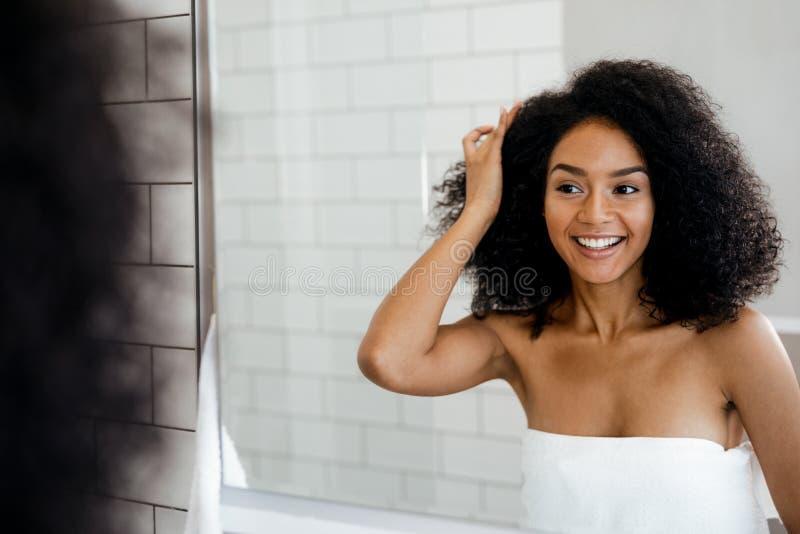 Jeune femme de sourire examinant ses cheveux images stock
