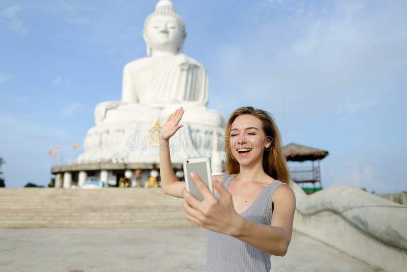 Jeune femme de sourire faisant l'appel visuel par le smartphone et montrant à Bouddha la statue blanche à Phuket photo stock