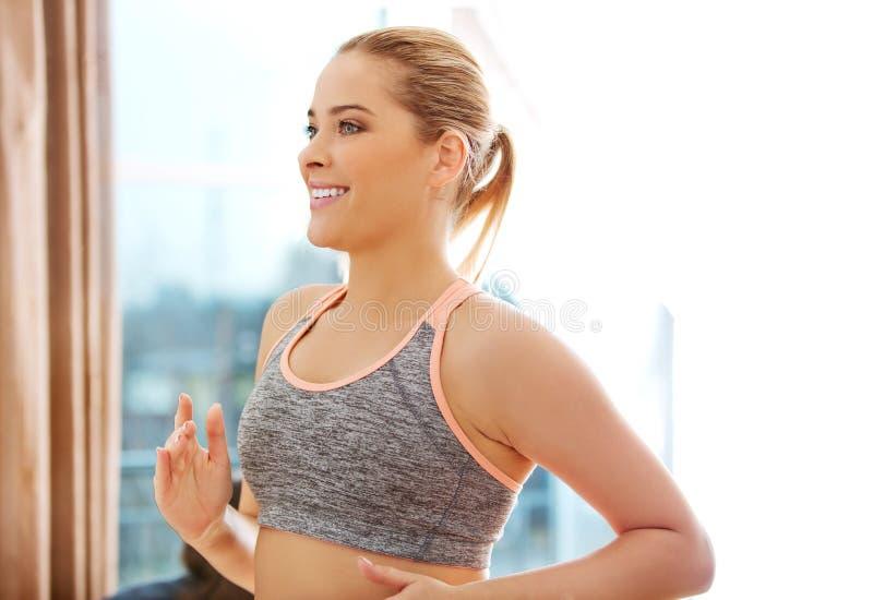 Jeune femme de sourire faisant l'exercice - courant en place photographie stock libre de droits