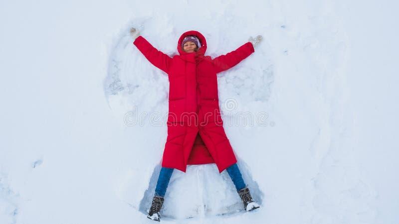 Jeune femme de sourire faisant un ange de neige photos stock