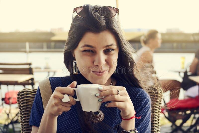 Jeune femme de sourire heureuse avec la tasse de café se reposant en café dehors récréation images libres de droits