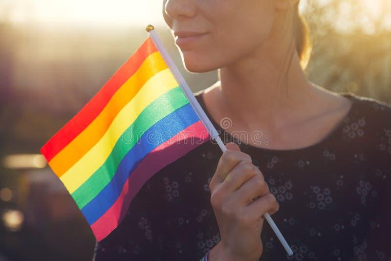 Jeune femme de sourire heureuse avec le bracelet de ruban d'arc-en-ciel sur sa main tenant le drapeau coloré d'arc-en-ciel de lgb image libre de droits