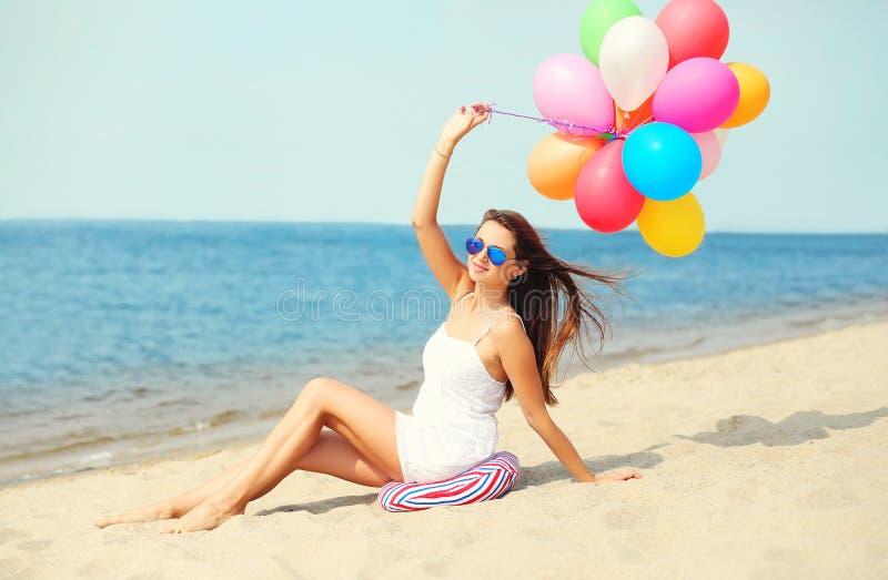 Jeune femme de sourire heureuse avec les ballons colorés sur la plage photographie stock