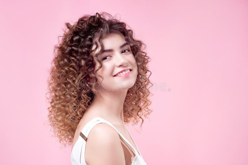 Jeune femme de sourire heureuse avec les cheveux bouclés d'éclat de coiffure étonnante dans la chemise blanche image stock