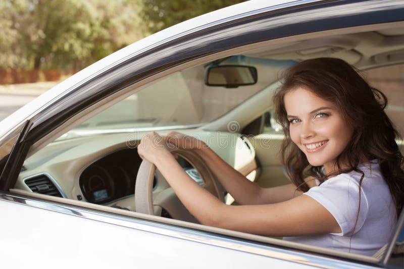 Jeune femme de sourire heureuse conduisant la voiture images stock