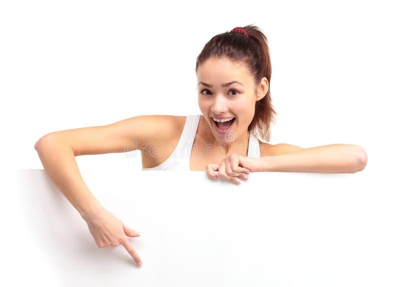 Jeune femme de sourire heureuse d'affaires affichant l'enseigne blanc image stock