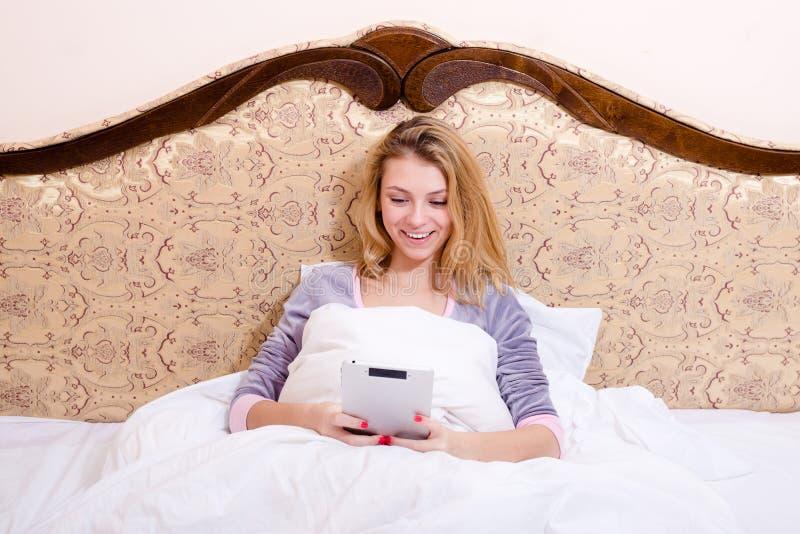 Jeune femme de sourire heureuse d'affaires dans le lit avec le portrait de sourire heureux d'ordinateur de PC de comprimé photo stock