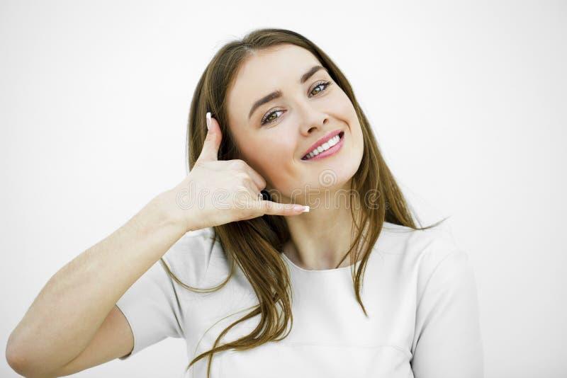 Jeune femme de sourire heureuse de brune avec l'appel je geste photo libre de droits
