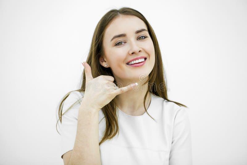 Jeune femme de sourire heureuse de brune avec l'appel je geste photographie stock libre de droits