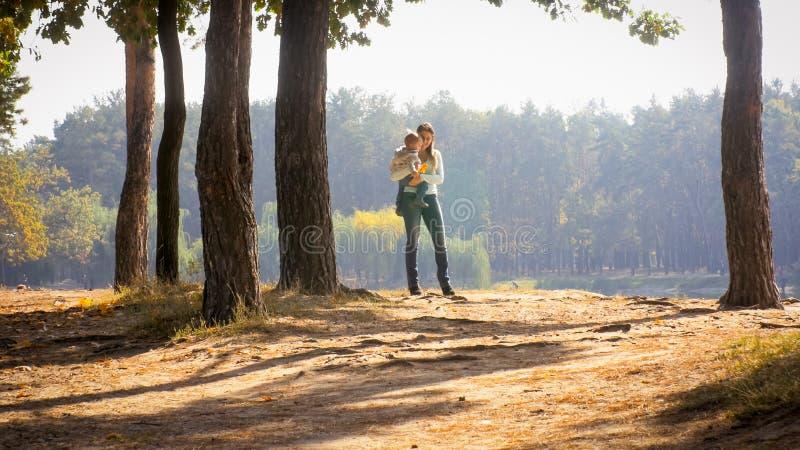 Jeune femme de sourire heureuse embrassant son fils d'enfant en bas âge au parc d'automne photos libres de droits