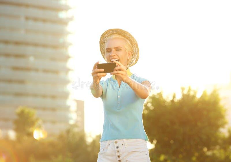 Jeune femme de sourire heureuse prenant le portrait de selfie dehors images stock