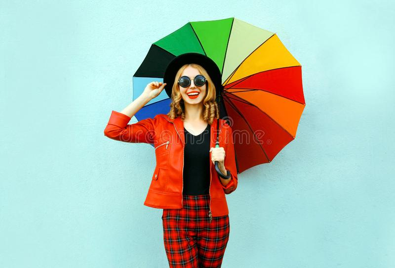 Jeune femme de sourire heureuse tenant le parapluie coloré dans des mains, veste rouge de port, chapeau noir sur le mur bleu photographie stock