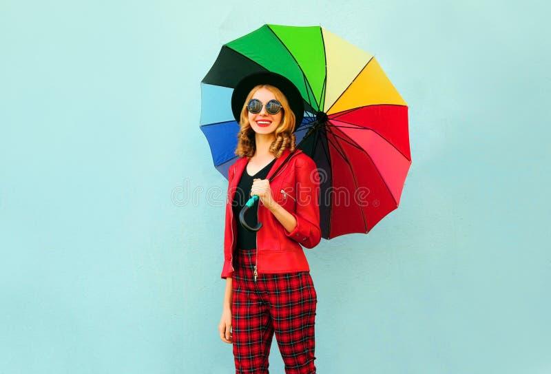 Jeune femme de sourire heureuse tenant le parapluie coloré dans des mains, veste rouge de port, chapeau noir sur le mur bleu photographie stock libre de droits