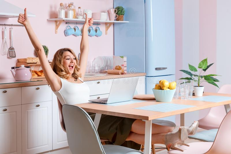 Jeune femme de sourire ? l'aide de l'ordinateur portable dans la cuisine ? la maison La femme blonde travaille ? travailler d'ord photos libres de droits