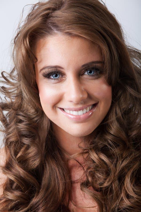Jeune femme de sourire mignonne avec de longs cheveux bouclés sains image stock